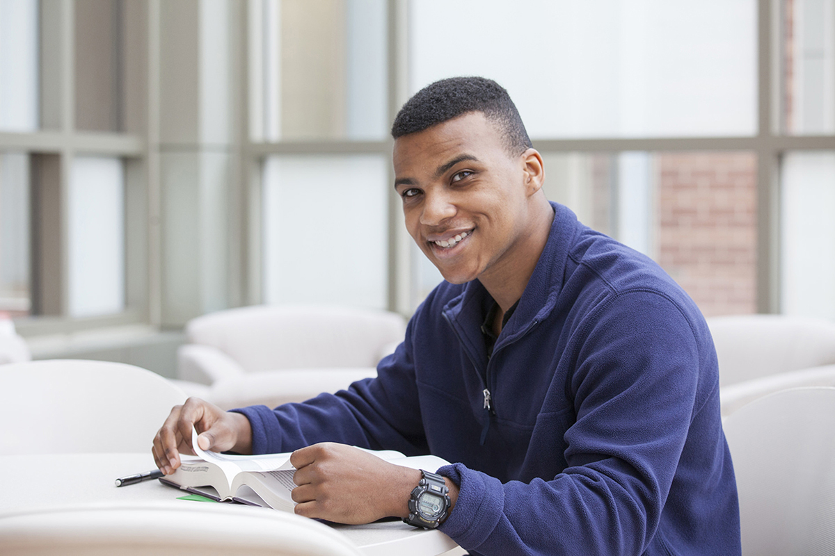 Young man smiling while studying
